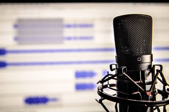 A microphone for recording with a screen behind with audio files on it