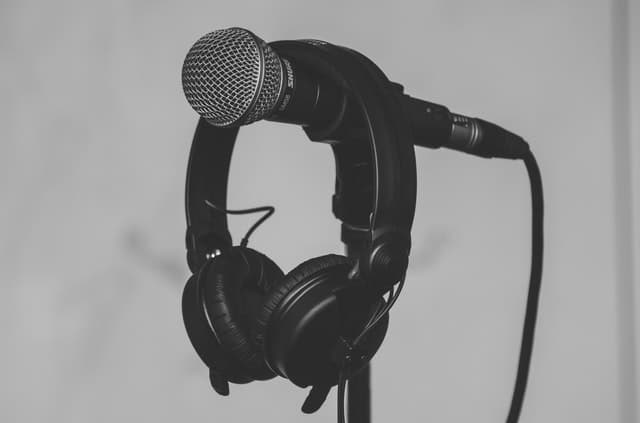Black headphones hanging on a black and gray microphone